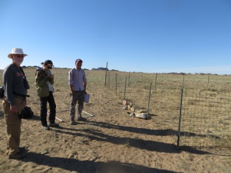 Two other Mongolian graduate students studying an exclosure which excludes grazing animals in an attempt to assess the damage grazing pressure has on natural communities.