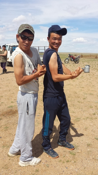 """Two of the young Mongolian graduate students that we worked with show off their """"guns"""" for the camera."""