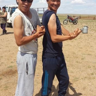 "Two of the young Mongolian graduate students that we worked with show off their ""guns"" for the camera."